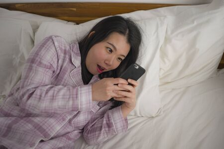 cozy lifestyle portrait of young beautiful and sweet Asian Korean woman in cute pajamas playful in bed using mobile phone enjoying social media or online dating app smiling happy and relaxed Reklamní fotografie
