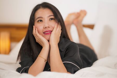 lifestyle portrait of young beautiful and sweet Asian Korean woman in bed feeling happy and relaxed wearing cute nightgown enjoying lazy Sunday morning at home playing cozy Reklamní fotografie