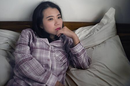 dramatic lifestyle portrait of young attractive sad and depressed Asian Korean woman on bed awake at night feeling stressed and lost suffering depression problem in sadness and melancholy Banque d'images - 134690080