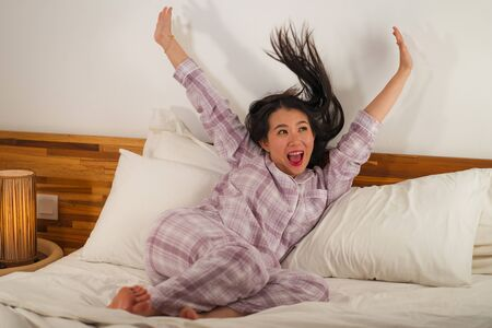 lifestyle portrait of young beautiful and sweet Asian Chinese woman in bed feeling happy and relaxed wearing cute pajamas enjoying lazy Sunday morning at home playing cozy Reklamní fotografie