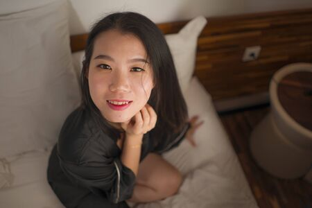 lifestyle portrait of young beautiful and sweet Asian Chinese woman in bed feeling happy and relaxed wearing cute nightgown enjoying lazy Sunday morning at home playing cozy