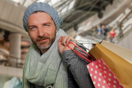 lifestyle portrait of young happy and attractive hipster man in winter hat and scarf smiling holding shopping bags purchasing gifts buying Christmas presents excited and cheerful at shopping mall 免版税图像