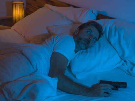 night edgy portrait of young stressed and paranoid American man lying on bed unable to sleep holding gun looking around scared feeling threatened suffering paranoia  in self protection concept