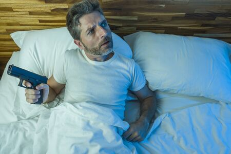 night edgy portrait of young stressed and paranoid American man lying on bed unable to sleep holding gun looking around scared suffering paranoia expecting intruders at home
