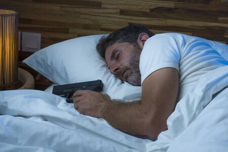night portrait of young stressed and paranoid American man in bed sleeping and holding gun fearing intruder breaking in home in paranoia and self defense concept Stock Photo