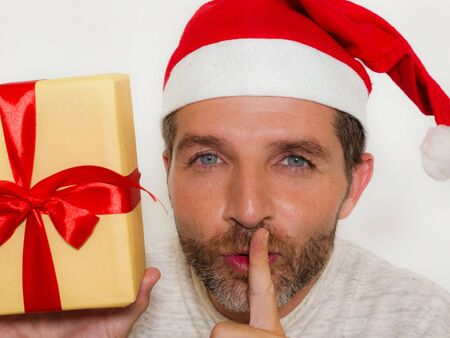 Christmas presents ! close up portrait of young happy and attractive man wearing Santa Claus hat holding xmas gifts and boxes smiling excited in holiday preparation on isolated background Stock Photo