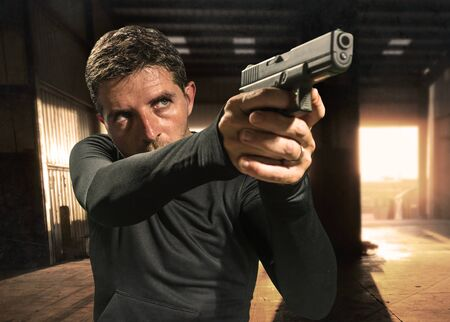 action portrait of serious and attractive hitman or special agent man holding gun pointing the weapon at cinematic edgy background in secret service movie Hollywood style Stock Photo