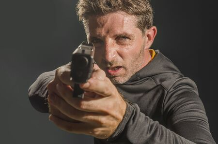 action portrait of angry and attractive hitman or special agent man holding gun pointing the weapon isolated on dark background in secret service Hollywood style movie