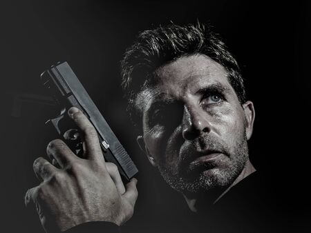 closeup portrait of serious and attractive hitman or special agent man holding gun isolated on black background in secret service Hollywood style movie and cinematic lighting