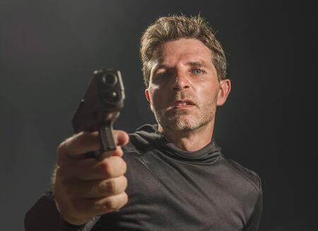 portrait d'action d'un tueur à gages en colère et attrayant ou d'un agent spécial tenant un pistolet pointant l'arme isolée sur fond sombre dans un film de style hollywoodien des services secrets Banque d'images