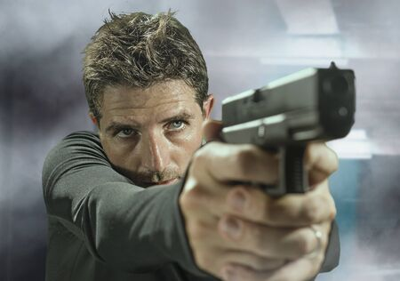 action portrait of serious and attractive hitman or special agent man holding gun pointing the handgun at cinematic edgy background in secret service movie Hollywood style