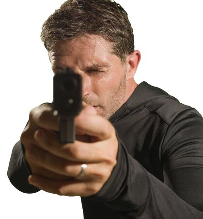 action portrait of serious and attractive hitman or special agent man holding gun pointing the handgun to the camera in Hollywood style movie isolated on studio background