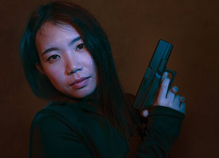 Asian girl with handgun - dramatic portrait of young attractive and dangerous looking Chinese woman holding gun posing playful dark grunge background and cinematic style in sexy killer concept