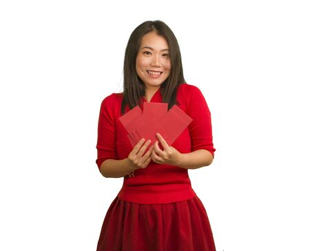 young beautiful and happy Asian Chinese woman in traditional New Year red dress and hair bun holding red pocket envelopes with money enjoying cheerful the blessing from friends and family