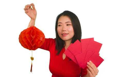 portrait of young beautiful and happy Asian Korean woman holding traditional blessing red pocket envelopes with money and red lantern celebrating excited Chinese new year in China tradition concept