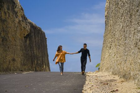 young happy and beautiful Asian Korean couple in love enjoying outdoors romantic journey walking in cliff rock road exploring the landscape together in holidays travel adventure and wanderlust