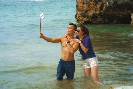 Summer holidays lifestyle portrait of young happy and playful Asian Chinese couple enjoying at the beach taking stick selfie photo with hand phone enjoying the sea together