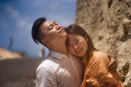 young happy and beautiful Asian Korean couple in love enjoying outdoors romantic journey playing sweet in cliff rock road exploring together in holidays travel adventure and wanderlust