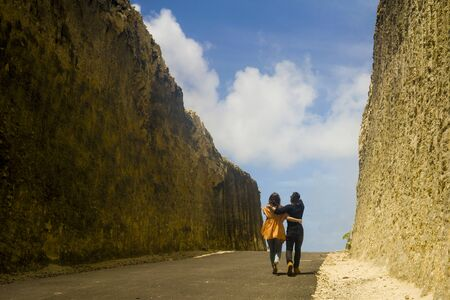 back view young happy and beautiful couple in love enjoying outdoors journey walking playful in cliff rock road exploring the landscape together in holidays travel adventure and wanderlust