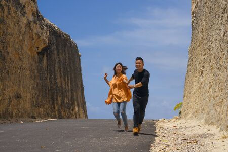 young happy and beautiful Asian Chinese couple in love enjoying outdoors journey running playful in cliff rock road exploring the landscape together in holidays travel adventure and wanderlust Zdjęcie Seryjne
