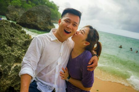 Summer holidays lifestyle portrait of young beautiful and sweet Asian Korean couple in love walking on the beach together enjoying honeymoon trip in the beach smiling cheerful and loving