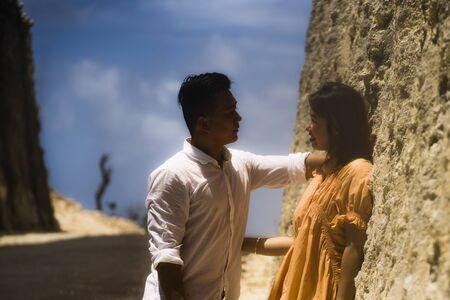 young happy and beautiful Asian Chinese couple in love enjoying outdoors romantic journey playing sweet in cliff rock road exploring together in holidays travel adventure and wanderlust