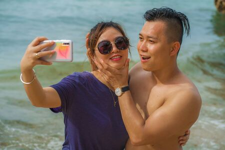 Summer holidays lifestyle portrait of young happy and playful Asian Chinese couple tourist enjoying at the beach taking selfie photo with hand phone enjoying sea together
