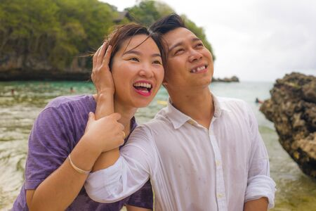 Summer holidays lifestyle portrait of young beautiful and sweet Asian Chinese couple in love walking on the beach together enjoying honeymoon trip in the beach smiling cheerful and loving