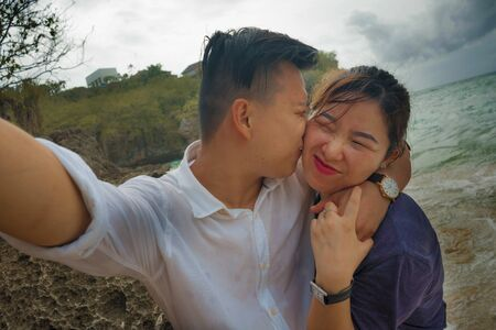 Summer holidays lifestyle portrait of young happy and playful Asian Korean couple tourist enjoying at the beach taking selfie photo with hand phone enjoying sea together