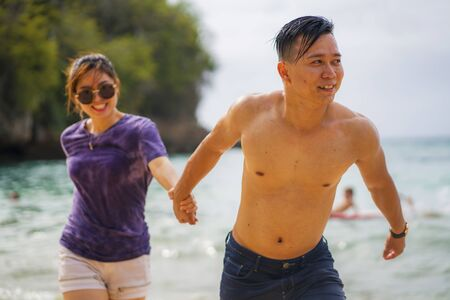 Summer holidays lifestyle portrait of young beautiful and sweet Asian Chinese couple in love running on the beach together enjoying honeymoon trip in the beach smiling cheerful and loving