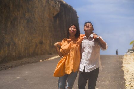 young happy and beautiful Asian Chinese couple in love enjoying outdoors romantic journey walking in cliff rock road exploring the landscape together in holidays travel adventure and wanderlust