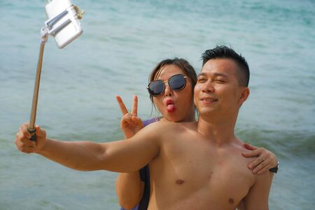 Summer holidays lifestyle portrait of young happy and playful Asian Korean couple enjoying at the beach taking stick selfie photo with hand phone enjoying the sea together