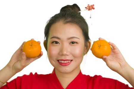 young beautiful and happy Asian woman in traditional Chinese New Year red dress holding orange fruit as symbol of prosperity isolated on white background in China culture tradition concept