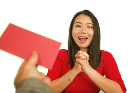 young beautiful and happy Asian woman in traditional Chinese New Year red dress receiving red pocket envelope with money enjoying cheerful blessing from friends and family