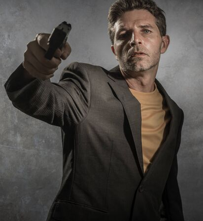 grunge cinematic portrait of attractive and dangerous looking mafia hitman or secret service especial agent man in blazer pointing gun in crime mob and criminal lifestyle concept