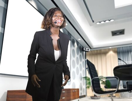 young attractive and confident successful black African American businesswoman with headset speaking at corporate company coaching and training at conference room for motivation