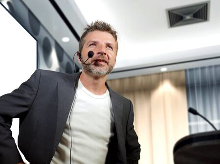 young attractive and confident successful businessman with headset speaking at corporate company coaching and training at conference room giving motivation for business success Stock Photo