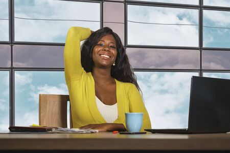 young happy and attractive black African American business woman smiling confident working at office computer desk in successful businesswoman celebrating corporate job success