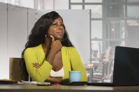 young attractive and thoughtful black afro American business woman working at office computer desk looking away thinking and pensive at cubicle workplace in corporate job lifestyle concept