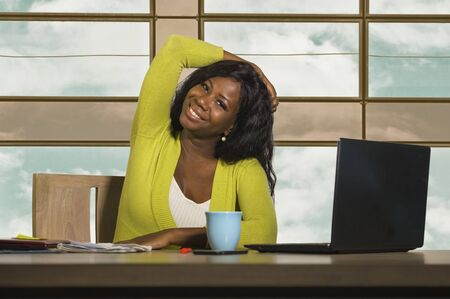 young happy and attractive black afro American business woman smiling confident working at office computer desk in successful businesswoman celebrating corporate job success