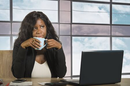 young beautiful and attractive black African American business woman thoughtful and pensive working at office computer desk drinking coffee in businesswoman executive job concept Stock Photo