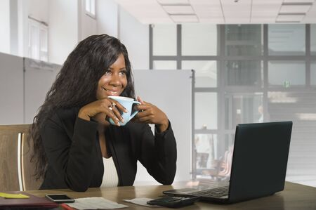 young beautiful and happy black African American business woman working at office computer desk drinking coffee smiling cheerful as successful businesswoman of corporate company Stock Photo