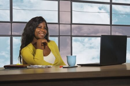 young happy and attractive black afro American business woman smiling confident working at office computer desk in successful businesswoman and corporate job success concept Stock Photo