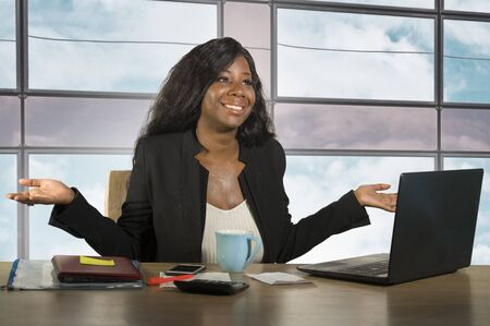 young happy and attractive black African American business woman smiling cheerful and confident working at office computer desk relaxed in successful businesswoman and job success concept