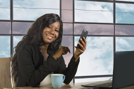 young happy and attractive black African American business woman smiling cheerful and confident working at office computer desk using mobile phone in successful businesswoman and success concept