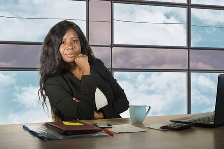 young happy and beautiful black African American business woman smiling cheerful and confident working at office computer desk relaxed in successful businesswoman and job success concept