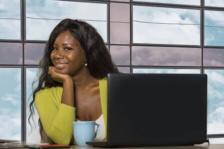 young happy and attractive black African American business woman smiling confident working at office computer desk in successful businesswoman and corporate job success concept