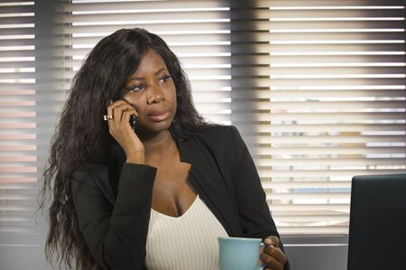 young beautiful and attractive black African American business woman talking serious on mobile phone working at office computer desk drinking coffee in businesswoman executive job concept