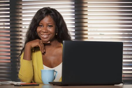 young happy and attractive black afro American business woman smiling cheerful and confident working at office computer desk relaxed in successful businesswoman and job success concept