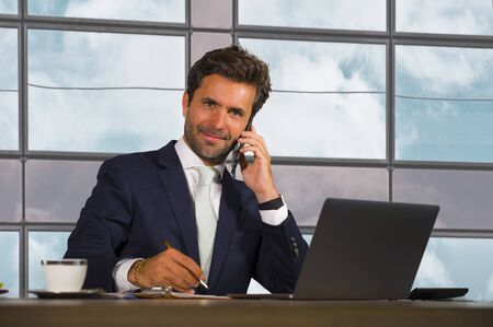 corporate business portrait of young happy and attractive latin businessman in suit and tie working at modern financial company smiling confident as successful executive man at work